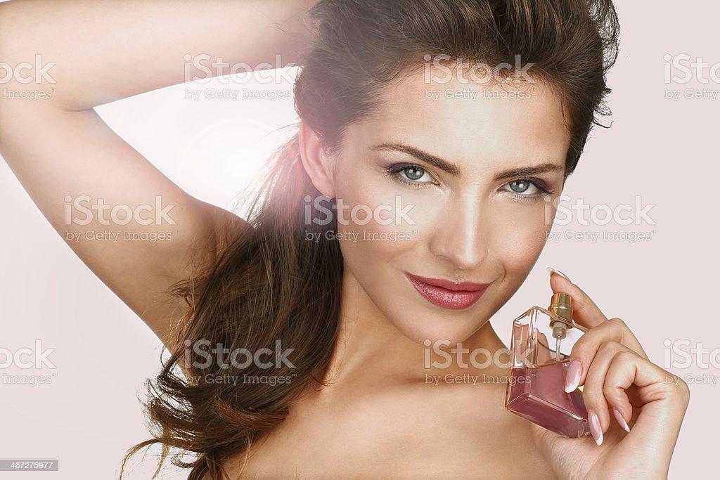 Primer plano de una hermosa mujer aplicar perfume - foto de stock