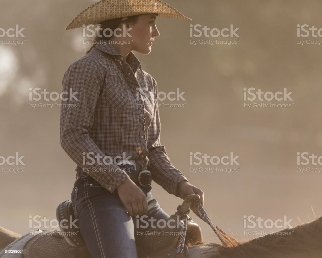 Close-up of a beautiful young cowgirl horseback riding on a Utah ranch. stock photo