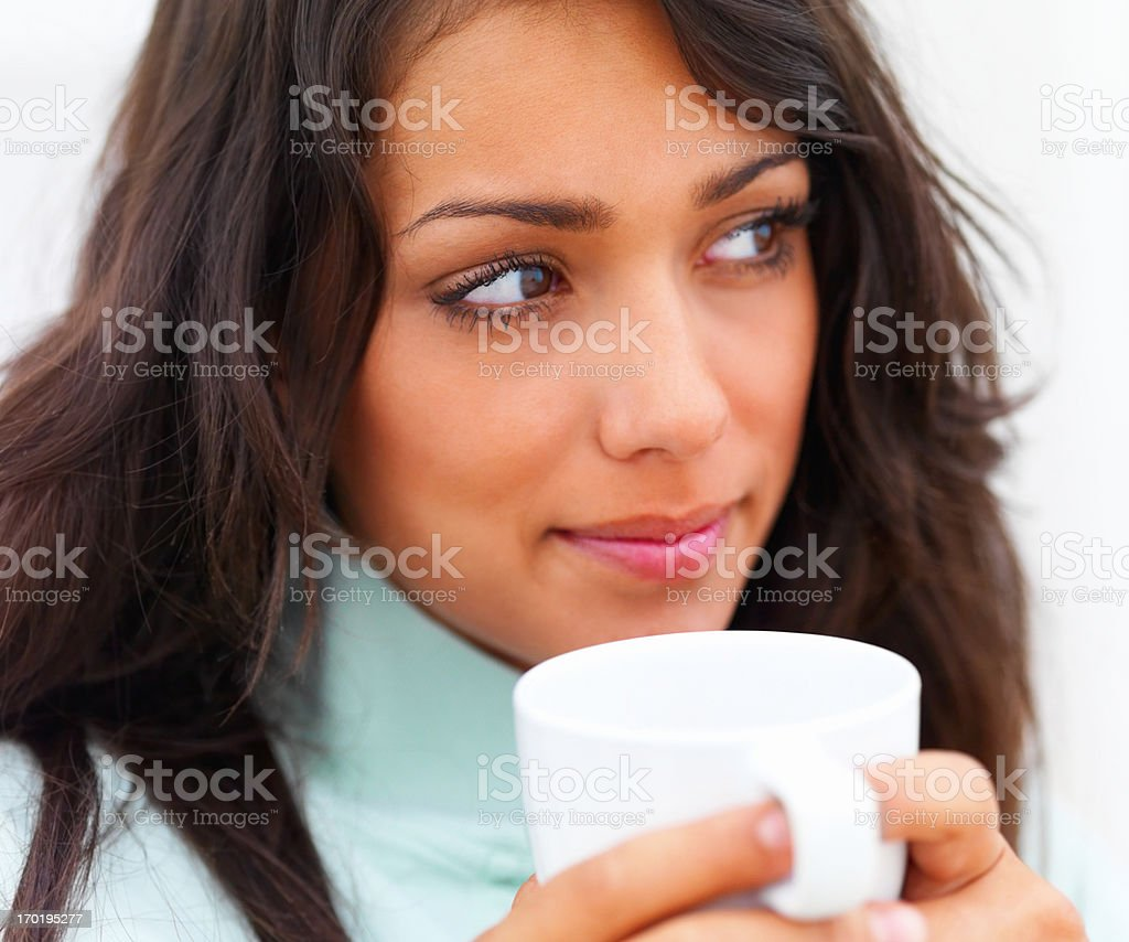 Closeup of a beautiful young lady holding coffee cup and looking away royalty-free stock photo