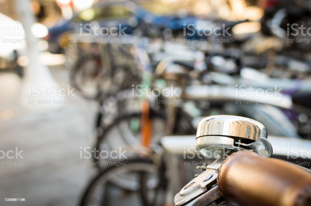 closeup of a bicycle handle bar and bell on an unfocused background of a bicycle parking in the center of the city of Gijón, Asturias, Spain.. stock photo