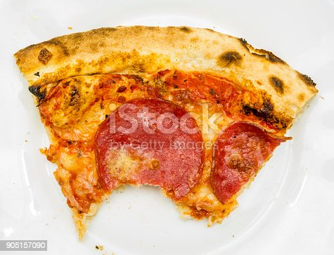 Closeup of a bitten portion of pepperoni pizza on a white plate.