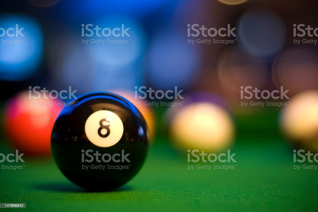 Close-up of a black 8 ball with blurred pool balls behind stock photo