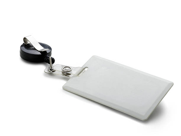 Close-up of a blank, white clip-on security pass White, plain, rectangular security ID badge with a round black and silvertone clip.  The badge is isolated on a white background and casts a shadow.  The clip and badge are connected with a clear plastic connector with silvertone metal fasteners.  A clipping path is included. cardkey stock pictures, royalty-free photos & images