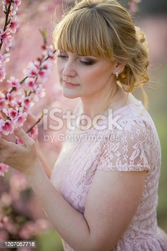 1054970060 istock photo Close-up of a blonde girl with brown eyes in a spring robe color dress near a young peach tree 1207057718