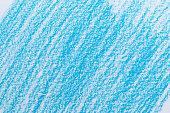 Close-up of a blue colored scribble with wax colored crayon on a white sheet of paper