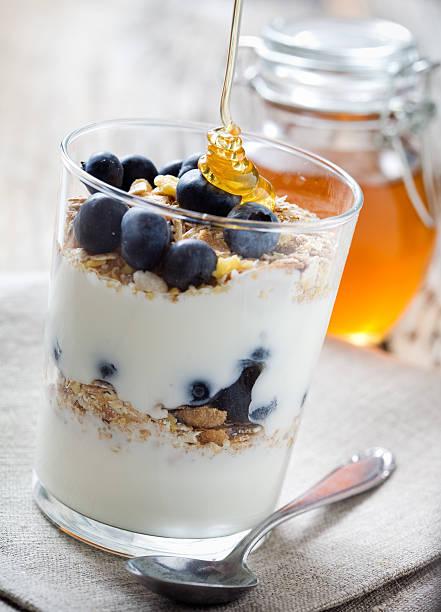 Close-up of a blueberry yogurt parfait with honey stock photo