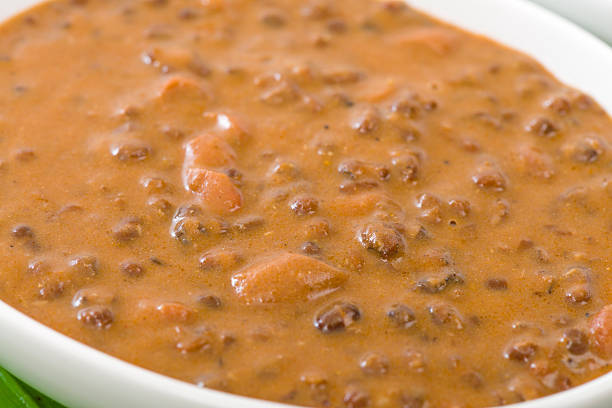 Close-up of a bowl of Dal Makhani in a white serving bowl Indian dish made with black lentils and spices. Traditional Punjabi cuisine. dal makhani stock pictures, royalty-free photos & images