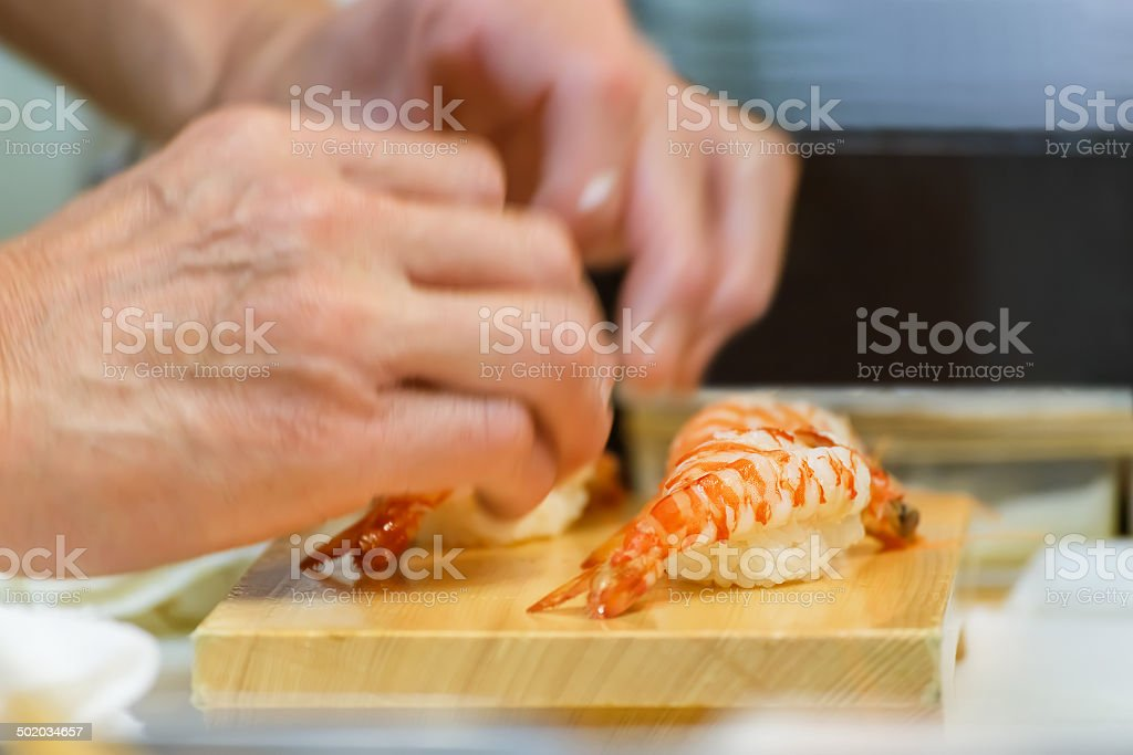 Closeup of a bowl of Sashimi with hands of Japanese chef stock photo