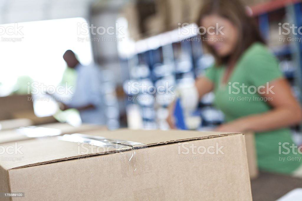 Closeup of a box being shipped in busy warehouse royalty-free stock photo