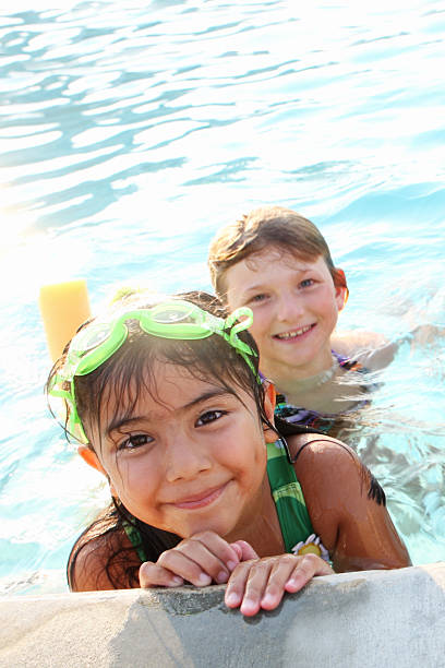 Close-up of a boy and girl in the swimming pool stock photo