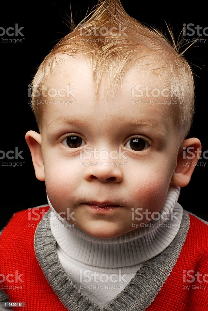 Close-up of a boy in red vest looking up serious royalty-free stock photo