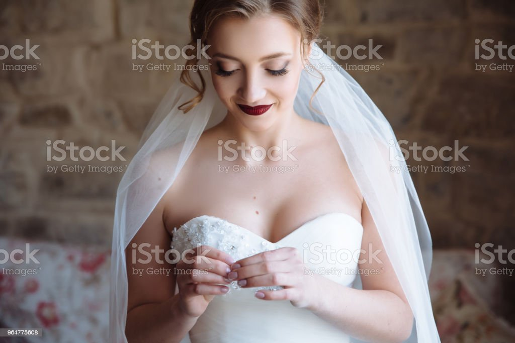 Close-up of a bride in an open dress is embarrassed and smiling. Bright lip makeup emphasizes the subtle features of the model's face royalty-free stock photo