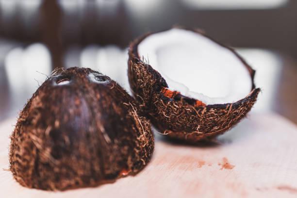 nahaufnahme einer gebrochenen kokosnuss - kokoskuchen stock-fotos und bilder