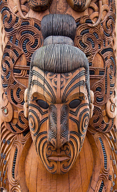 close-up of a brown and black maori carving of a man - maori stock photos and pictures