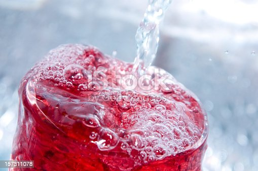 A refreshing juice drink mixed with ice cold spring water. Shallow DOF, with main focus on front surface of drink.
