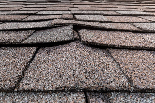 A close-up of a buckled residential asphalt shingled roof A close-up view of a residential roof with architectural asphalt shingles that are buckled which can be signs of water damage and poor workmanship. The buckling of the shingles could be signs of the sheathing can be warping or delaminating from water penetration, which leads to a reroof. replacement stock pictures, royalty-free photos & images