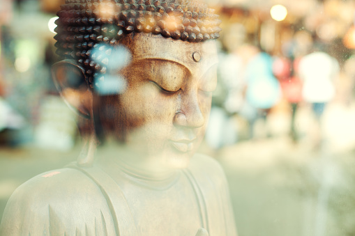 Close up of a Sri Lankan wooden Buddha statue in a window display.