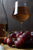 A close-up of a bunch of grapes, and in the background a bottle and a glass of pink wine are out of focus. vertical orientation.