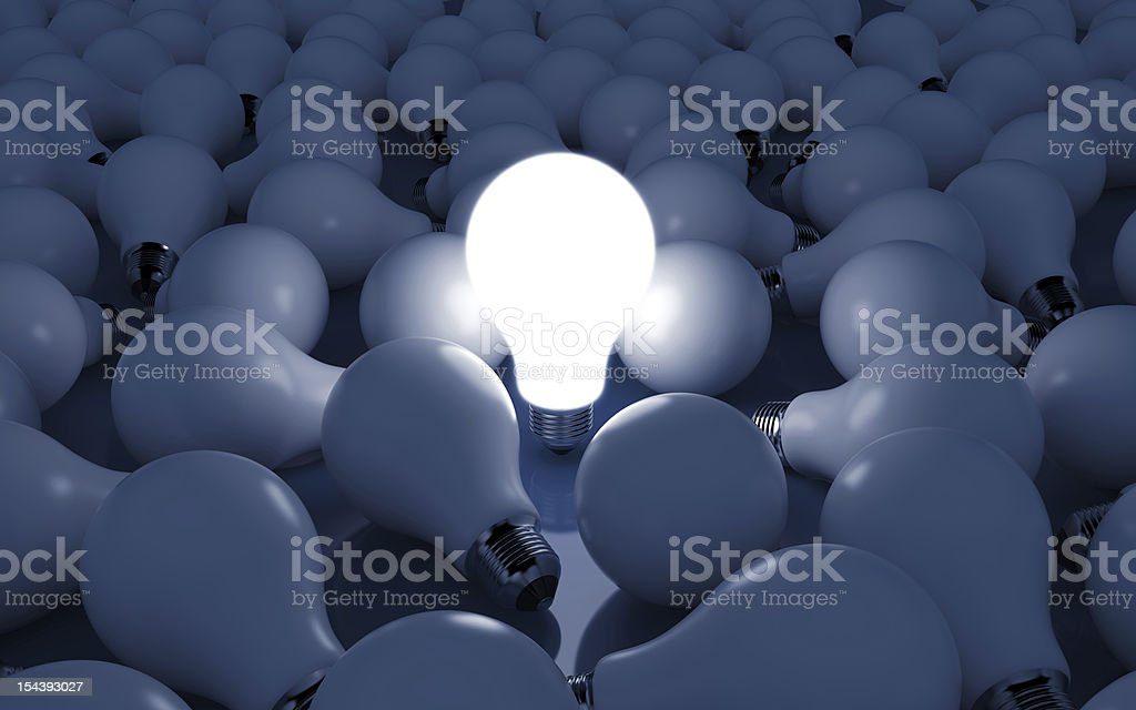 A close-up of a bunch of light bulbs with one lit royalty-free stock photo