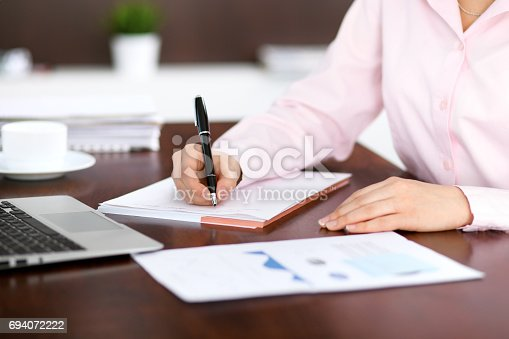 istock Closeup of a business woman writing in a notebook 694072222
