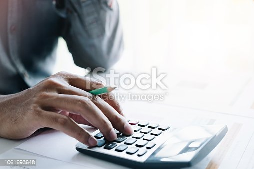 Closeup of a businessman financial specialist is working with calculator and computer to analyze a lot of data on financial report