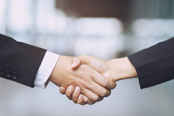 plan rapproché d'une main d'homme d'affaires secouez la femme d'affaires entre deux collègues ok, réussissez en affaires tenant des mains. - se saluer photos et images de collection