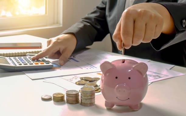 primer plano de una empresaria sosteniendo una moneda en una alcancía, un concepto de ahorro de dinero para la contabilidad financiera. - gerente de cuentas fotografías e imágenes de stock