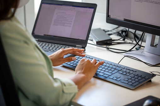 Close-up of woman typing on computer keyboard at workplace. Businesswoman using desktop computer in office.