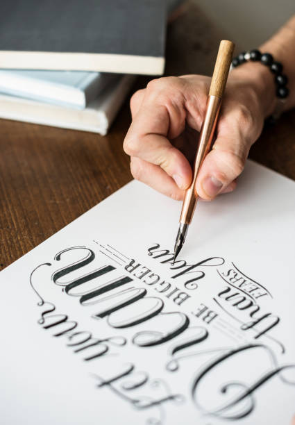Closeup of a calligrapher working on a project - foto stock