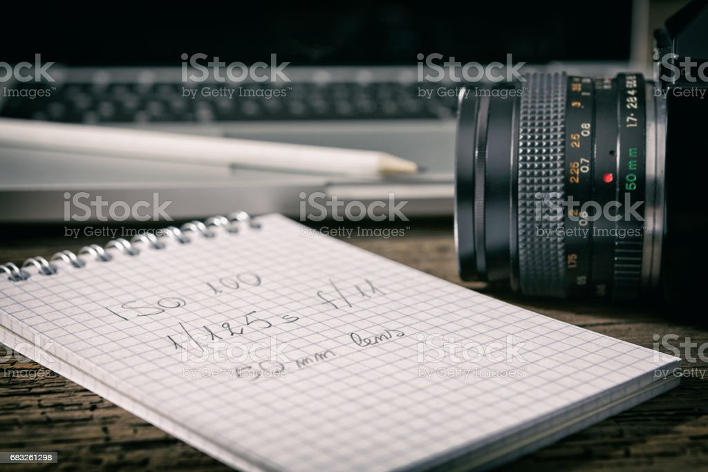 Closeup of a camera and a written notebook royalty-free stock photo