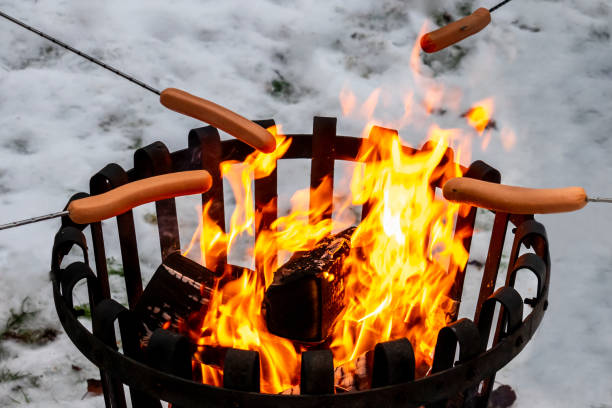 Closeup of a campfire with hot dog food over open fire. Winter snow outdoor scene. stock photo
