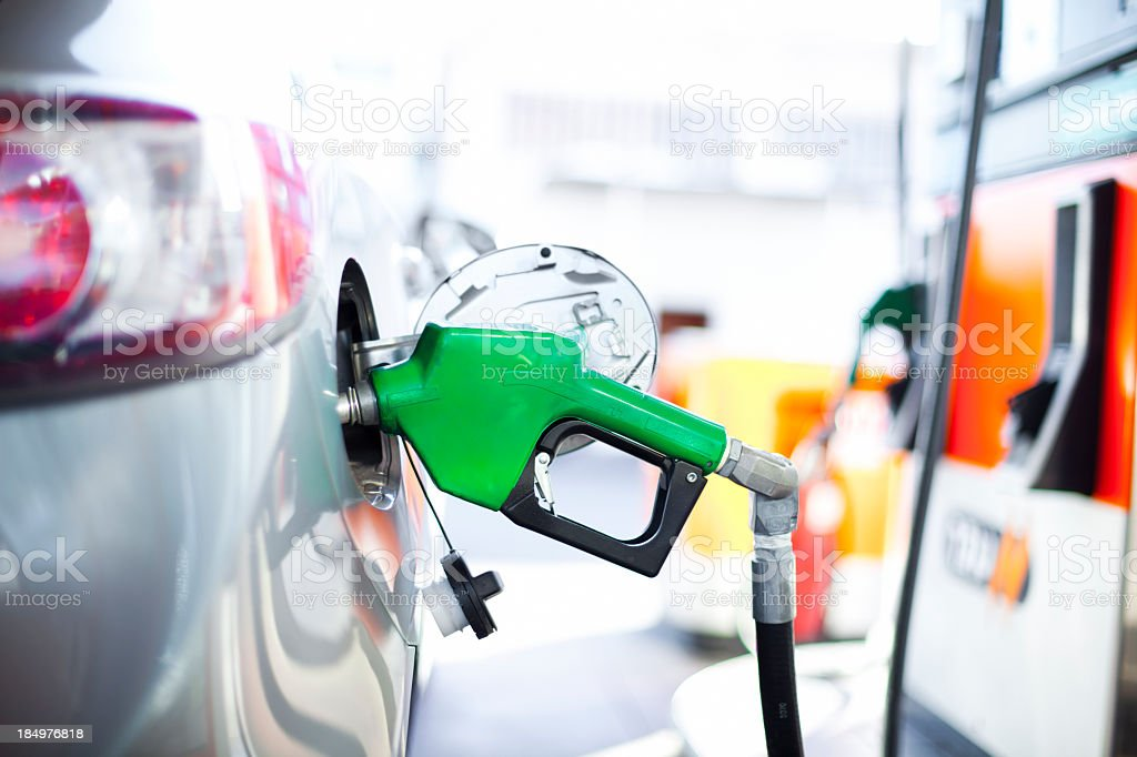 A close-up of a car being filled with gas stock photo