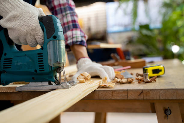 Close-up of a carpenter using a circular saw to cut a large board of wood stock photo