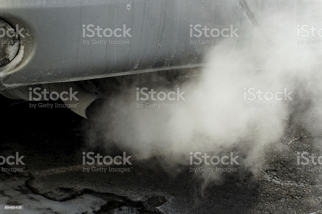 Close-up of a car's tailpipe with smoke coming out  royalty-free stock photo