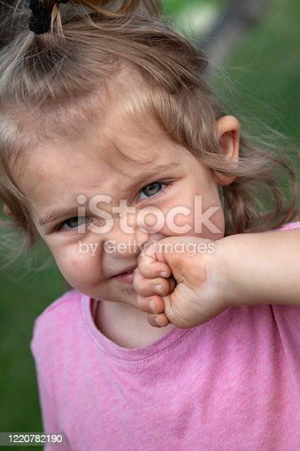 Portrait of a displeased little girl touching her mouth with fist