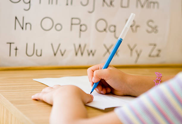 A closeup of a child writing the alphabet with a blue marker stock photo