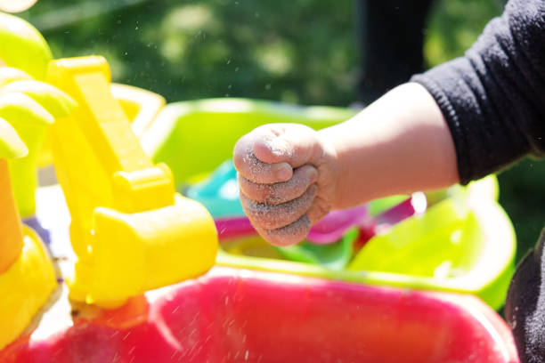 Close-up of a child's hand holding sand in a palm above toy table. stock photo