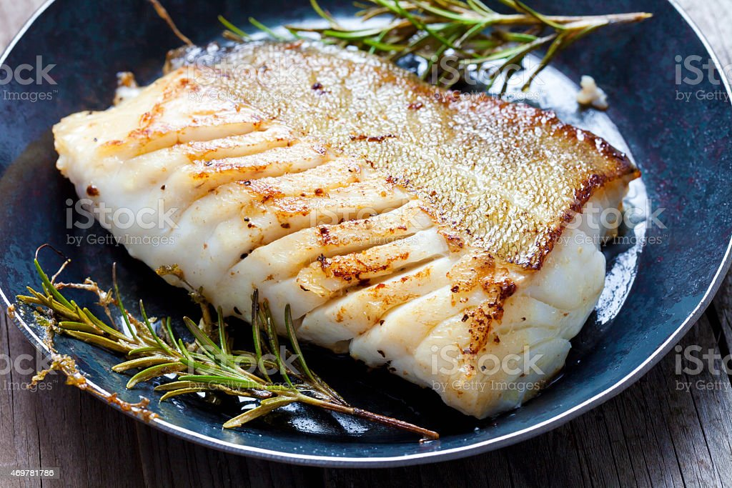 Close-up of a cod fillet with rosemary on a plate stock photo