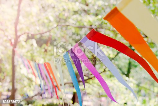 istock Closeup of a colorful party banner tied between trees. 623378672