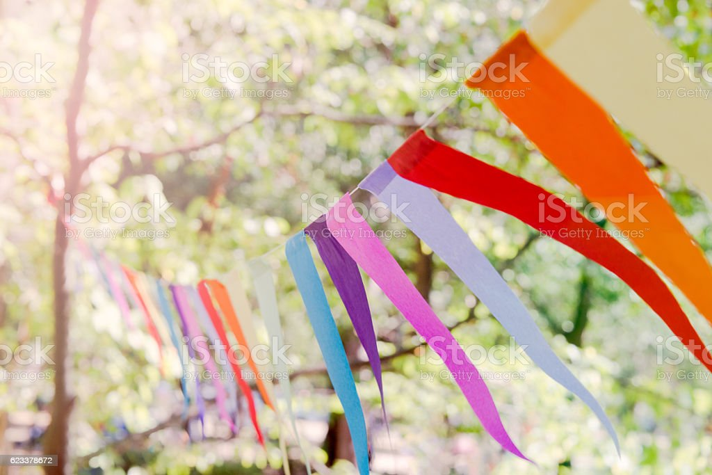 Closeup of a colorful party banner tied between trees. stock photo