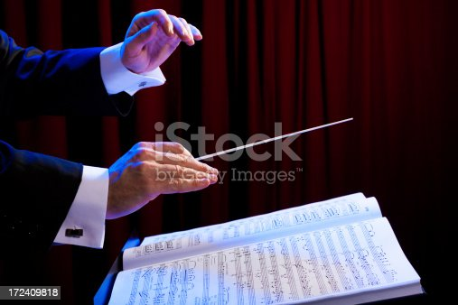 Conductor's hands with a baton and music score