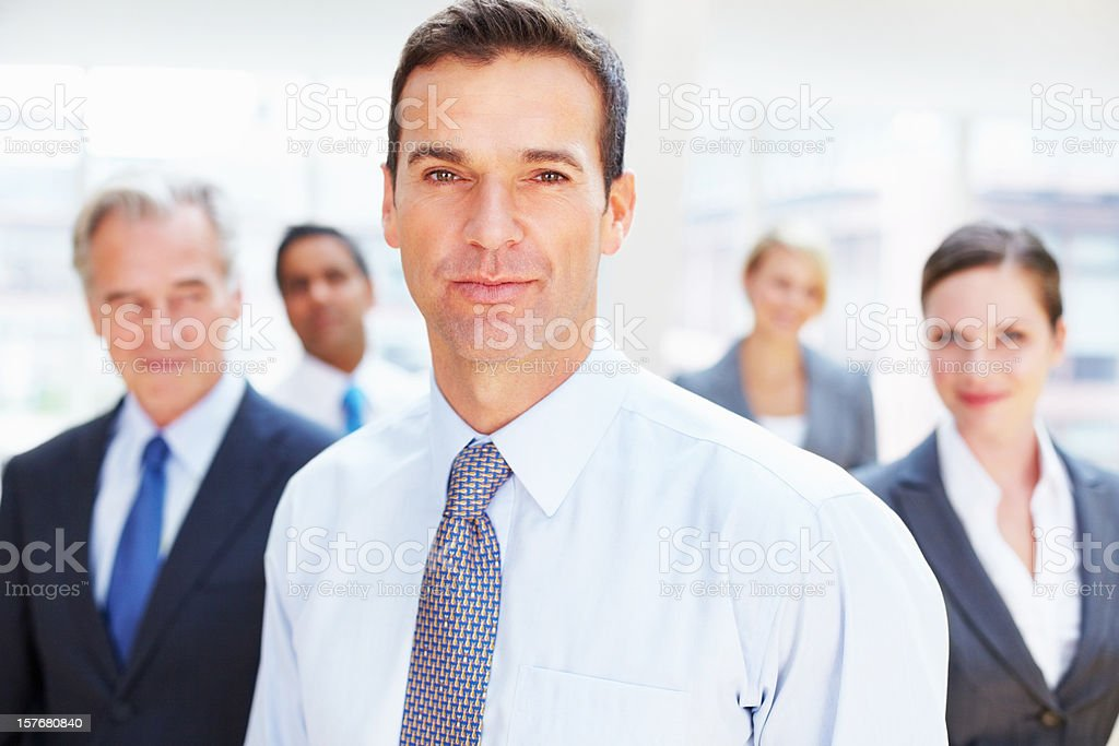 Closeup of a confident businessman with team in the background royalty-free stock photo