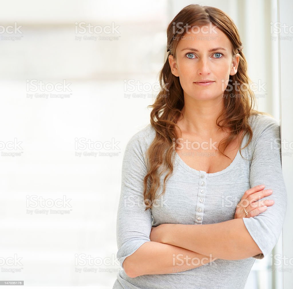 Close-up of a confident young woman with arms crossed stock photo