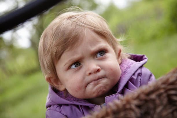 Close-up of a confused little girl looking to the right stock photo