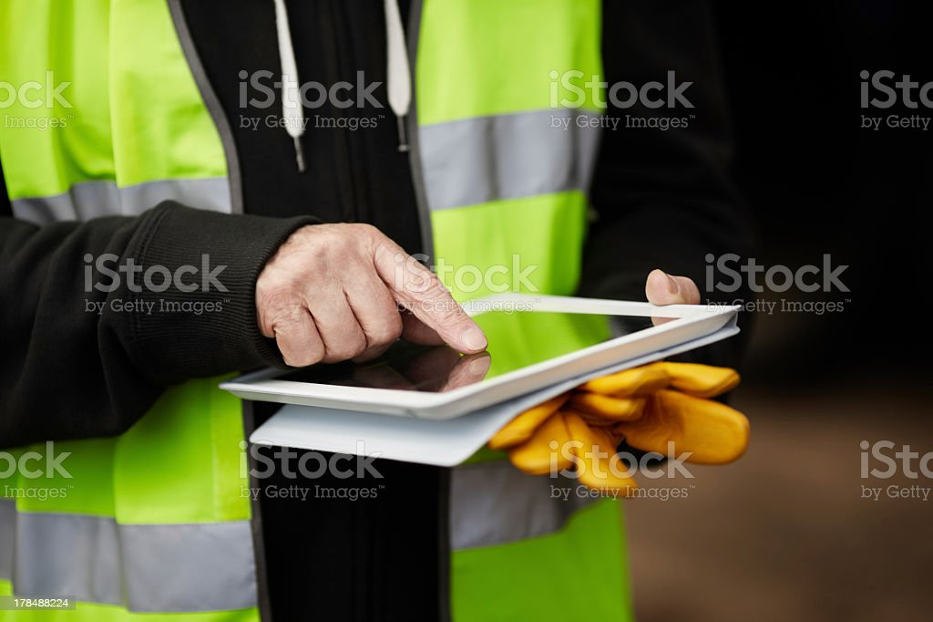 Close-up of a construction worker using digital tablet stock photo