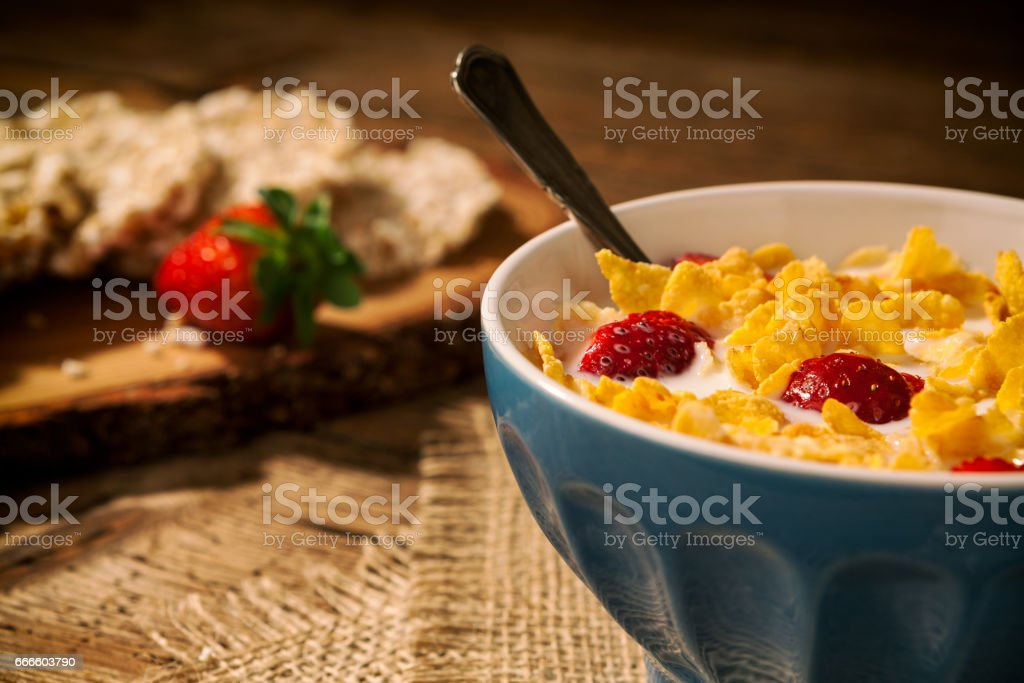 Closeup of a continental breakfast with cornflakes and strawberries in a cup of milk stock photo