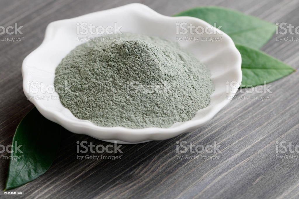 Gros plan d'une argile grise sec cosmétique dans un bol blanc sous la forme d'un coquillage sur une table en bois noir. Orné de feuilles vertes. - Photo