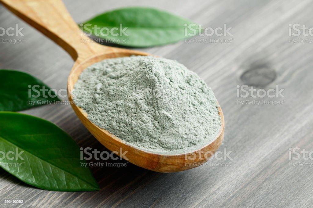 Primer plano de una arcilla gris seco cosmética en una cuchara de madera sobre una mesa de madera negra. Decorado con hojas de color verde. - foto de stock