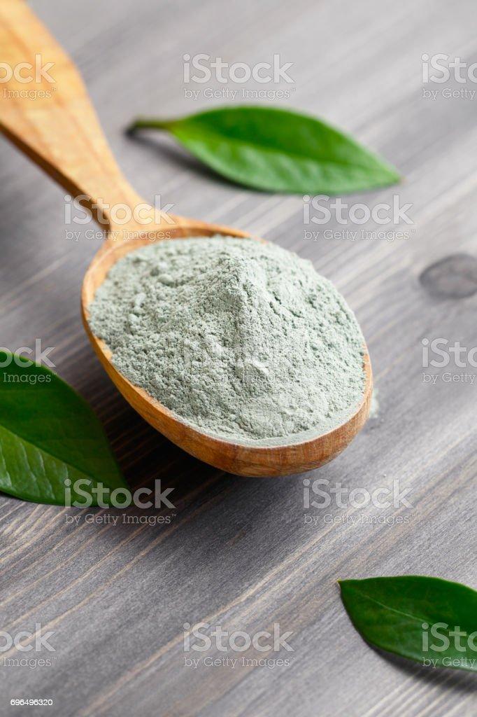 Gros plan d'une argile grise sec cosmétique dans une cuillère de bois sur une table en bois noire. Orné de feuilles vertes. - Photo