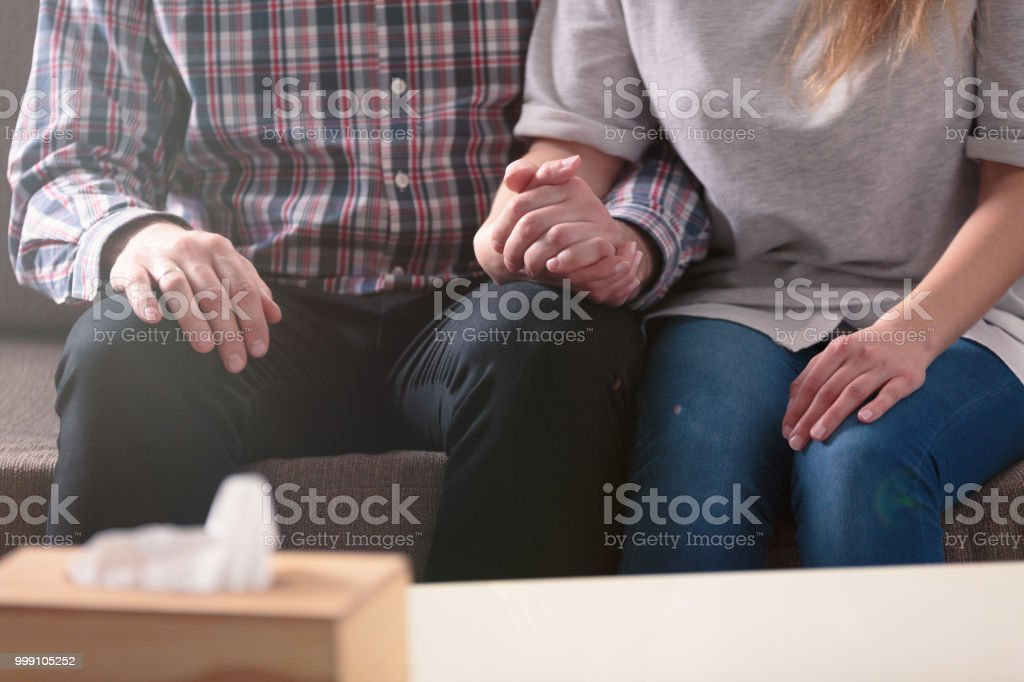 Close-up of a couple holding hands together while sitting on a couch during a therapy royalty-free stock photo